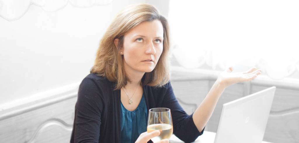 Woman with laptop looking frustrated while holding a glass of wine