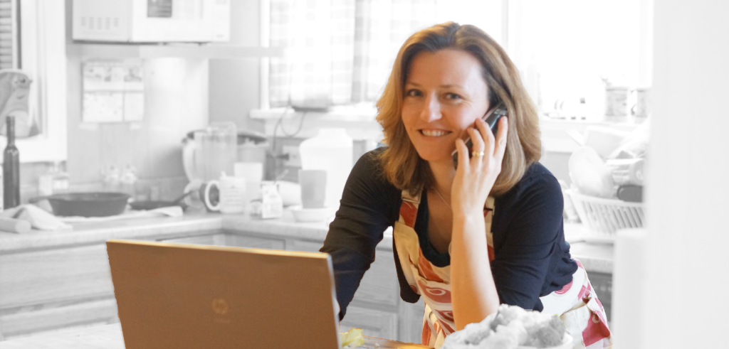 Woman in her kitchen on laptop talking on phone and smiling